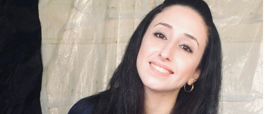 Picture of Nayrouz Qarmout. Smiling with dark long hair and in a black top, her head tilted to oneside.